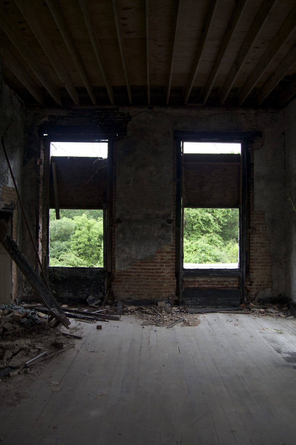 2nd floor bedroom with substantial fire damage. The exposed beams in the ceiling are from the new roof that was replaced after the fire in 2002.