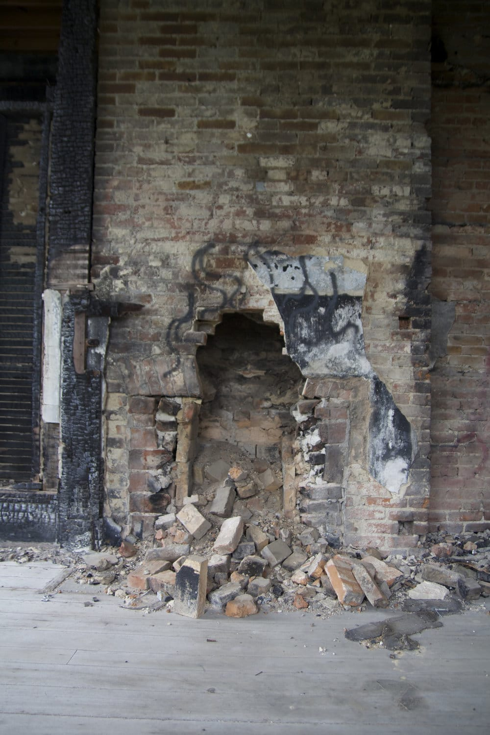Another view of a 2nd floor bedroom with fire damage to the wood portions of the room and vandalism to the interior hearth. I wonder how many cold evenings were warmed by this fireplace before heat and electricity were available.