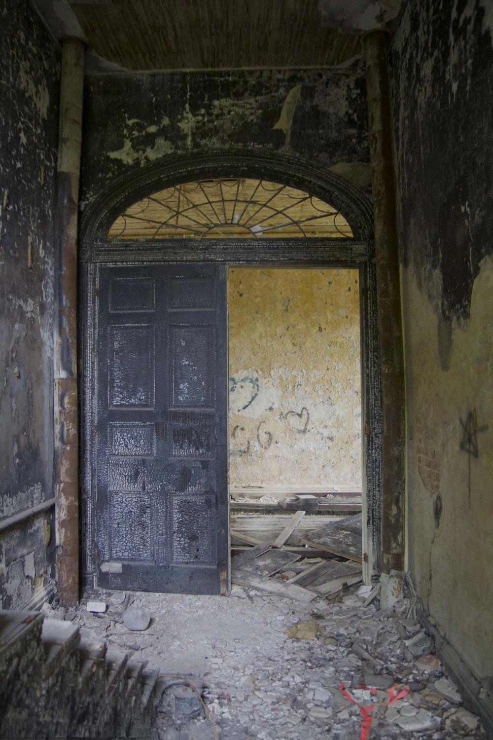 Doorway openings are trimmed with radiating brick voussoirs and with keystones and impost blocks of carved marble. Each opening contains a twelve-panel, single-leaf door, two sidelights with decorative muntins, and a fanlight with radiating, swag and oval muntins